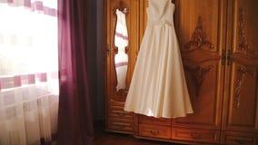 Vestito da sposa che appende nella stanza stock footage