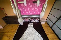 Vestito da sposa che si trova sul letto, sparante dal soffitto immagini stock libere da diritti