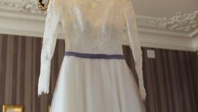 Vestito da sposa elegante su un gancio fatto specialmente per una cerimonia di nozze di giovane sposa video d archivio