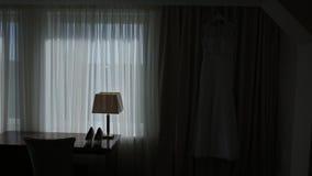 Vestito da sposa in hotel che appende su una parete con luce naturale video d archivio