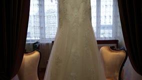 Vestito da sposa sul fondo della finestra video d archivio