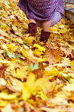 Vestito dai pattini dei piedini della donna in fogli di autunno Fotografie Stock Libere da Diritti