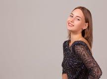 Vestito dal nero di ina della ragazza di Smilling su fondo bianco Fotografia Stock