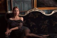Vestito dal nero di ina della ragazza nella stanza di lusso Fotografie Stock Libere da Diritti