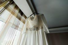 Vestito dal ` s della sposa che appende sullo scaffale vicino alla finestra nella sala immagine stock libera da diritti