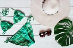 Vestito del bikini, cappello, occhiali da sole, stella di mare, foglia verde del plam sistemata su baclground di legno Concetto d fotografie stock