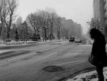 Vestito del centro e nero dalla strada della neve Fotografia Stock
