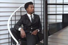 Vestito del nero del giovane e professionista di seduta dell'uomo d'affari delle scale del legame Immagine Stock Libera da Diritti