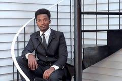 Vestito del nero del giovane e professionista di seduta dell'uomo d'affari delle scale del legame Fotografia Stock Libera da Diritti