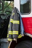 Vestito del pompiere che appende sulla porta del camion dei vigili del fuoco Fotografie Stock