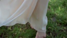 Vestito di seta d'uso dalla bella ragazza bionda che fila a piedi nudi sulla terra Nuziale, giorno delle nozze video d archivio
