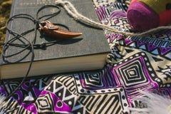 Vestito e libro che si trovano sulla terra asciutta Stile dei pantaloni a vita bassa Immagini Stock
