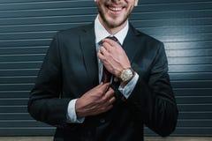 Vestito ed orologio d'uso dell'uomo d'affari, sorridendo e legando cravatta Fotografie Stock Libere da Diritti