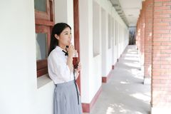 Vestito grazioso cinese asiatico felice dello studente di usura della ragazza in cola bevente della scuola in natura in primavera Immagini Stock