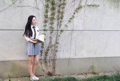 Vestito grazioso cinese asiatico felice dello studente di usura della ragazza in libro di lettura della scuola Fotografia Stock Libera da Diritti