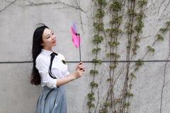 Vestito grazioso cinese asiatico felice dello studente di usura della ragazza a scuola che gioca mulino a vento Immagini Stock