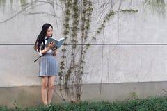 Vestito grazioso cinese asiatico felice dello studente di usura della ragazza a scuola che sorride e che legge un libro in natura Immagini Stock Libere da Diritti
