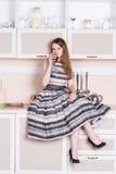 Vestito grigio fertile dalla ragazza che si siede nella cucina fotografia stock libera da diritti