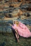 Vestito rosa sexy dalla sala da ballo della bella donna bionda che sta sulle rocce in Santorini Fotografia Stock