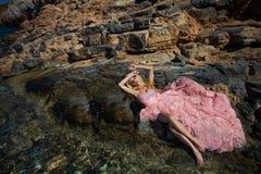 Vestito rosa sexy dalla sala da ballo della bella donna bionda che sta sulle rocce in Santorini Immagine Stock Libera da Diritti