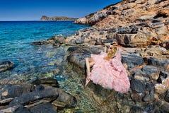 Vestito rosa sexy dalla sala da ballo della bella donna bionda che sta sulle rocce in Santorini Fotografie Stock