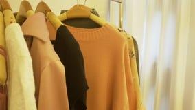 Vestuario casero de la tienda del guardarropa o de la ropa La mujer joven asiática que elige su equipo de la moda viste en armari metrajes