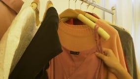 Vestuario casero de la tienda del guardarropa o de la ropa La mujer joven asiática que elige su equipo de la moda viste en armari almacen de video
