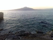 The Vesuvio seen from the Sorrento Peninsula-1. The Vesuvio seen from the Sorrento Peninsula, in the Gulf of Naples at sunset, only the blue sea separates from royalty free stock image