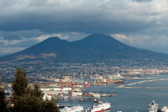 Vesuvius over Naples. Picture of the volcano behind the Naples sea port. Dark clouds resting on Vesuvius while the port is sunny. Great view of the Italian city Royalty Free Stock Photos