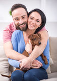 Vet. Beautiful young couple with their dog - zwergpinscher on their living room couch Royalty Free Stock Images