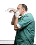 Vet blowing in a plastic glove in front of white Royalty Free Stock Photography