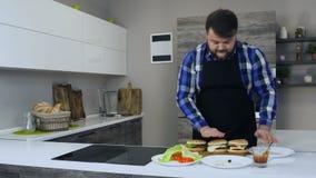 Of vet gebaard mannetje kookt dik een eigengemaakte hamburger in een moderne keuken stock videobeelden
