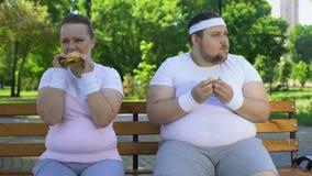 Vet jong paar die die hamburgers eten, aan ongezonde kost, gebrek worden gewijd aan wilskracht stock footage