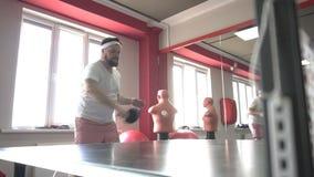 Vet Kaukasisch gebaard mensen speelpingpong in een moderne gymnastiek, het dumpen bovenmatig gewicht, langzame motie, vriendschap stock video