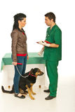 Vet man explaining owner treatment. Vet men explaining owner womanw ith dog the treatment for pet  in his office Stock Photo