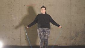 Vet meisje in de gymnastiek die met een springtouw werken stock videobeelden