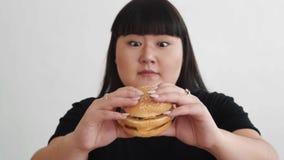 Vet meisje die een slechte hamburger houden en gelukkig snel voedsel ongezond voedsel stock video
