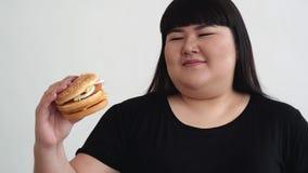 Vet meisje die een slechte hamburger houden en ongelukkig snel voedsel ongezond voedsel stock videobeelden