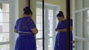Vet meisje in een blauwe kleding voor een spiegel stock footage
