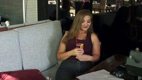 Vet meisje in koffiewinkel met limonade en een telefoon stock footage