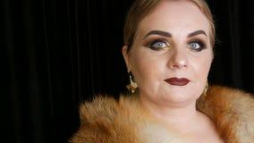 Vet vrouwelijk model met gouden make-up en rokerige ogen in een laag van vosbont en grote gouden oorringen die op zwarte stellen stock footage