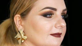 Vet vrouwelijk model met gouden make-up en rokerige ogen in een laag van vosbont en grote gouden oorringen die op zwarte stellen stock video