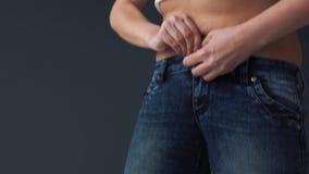 Vet vrouwenlichaam die op haar strakke jeans proberen te zetten stock videobeelden