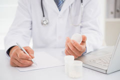 Vet writing on clipboard the prescriptions. In medical office Stock Photo
