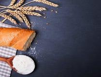 Vete, baquette och mjöl på det svarta brädet Arkivfoto