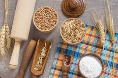 Vete och havre i behållaren, mjölet, skeden, kavlen och set Royaltyfria Bilder