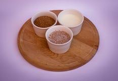 Vetekli, yoghurt och blandning av dem i vitbunkar på träplattan Fotografering för Bildbyråer
