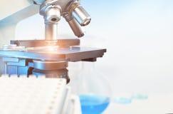 Vetenskaplig bakgrund med closeupen på det ljusa mikroskopet och blurr Arkivbilder