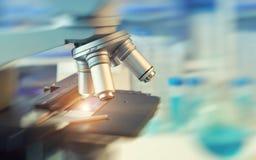 Vetenskaplig bakgrund med closeupen på det ljusa mikroskopet och blurr Arkivfoto