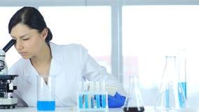 Vetenskapliga Reseacher genom att använda mikroskopet i laboratoriumet för experiment Arkivfoto